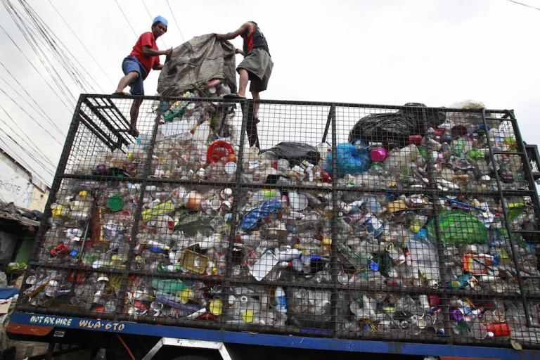 Workers load collected plastic bottles onto a truck in Manila in the Philippines, March 10, 2015.