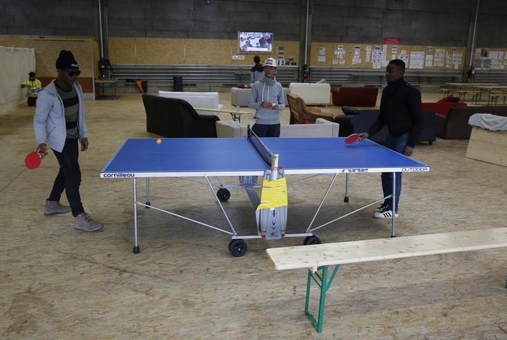 At an Army base in Thun, Zwitzerland, two young men play ping-pong at a blue table while a friend watches