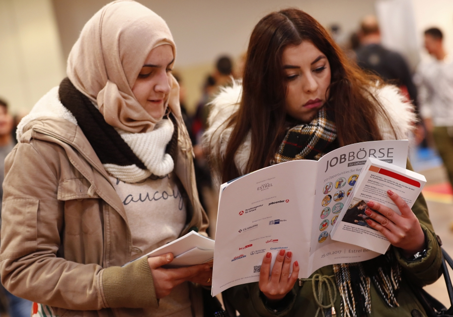 Two women visit a job fair for migrants and refugees in Berlin, Germany, Jan. 25, 2017.