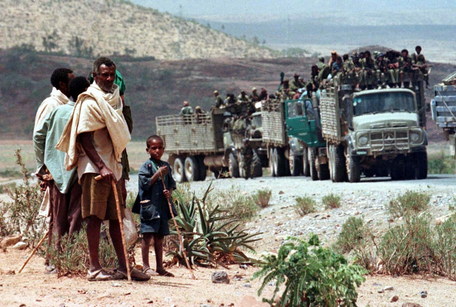 Herdsmen watch a convoy carrying Ethiopian soldiers pass on its way to the frontline at Zalambessa, as Ethiopian and Eritrean forces clashed near the disputed town of Badme, June 11, 1998.