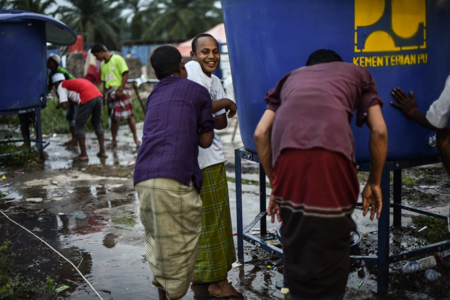 Muslim refugees wash before evening prayer at the Bayeun, East Aceh, Indonesia refugee camp on July 19, 2015.