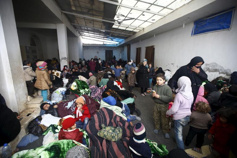 Internally displaced Syrians gather at a shelter near the Bab al-Salam crossing, bordering Turkey's Kilis province, on the outskirts of the northern border town of Azaz, Syria, Feb. 6, 2016.