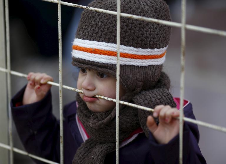 A Syrian boy looks through a gate as others wait to cross into Syria at the Oncupinar border crossing in Kilis, Turkey, Feb. 11, 2016.