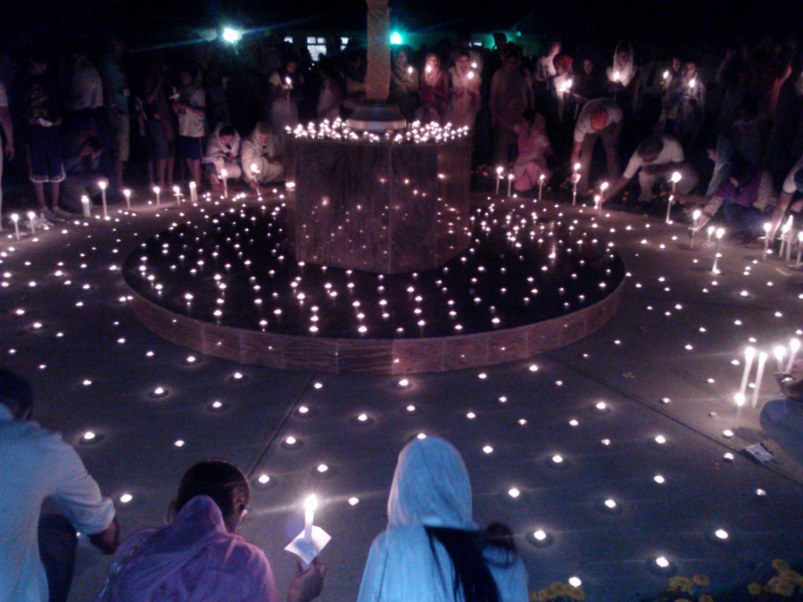 People sit around light candles, with scarves covering their heads