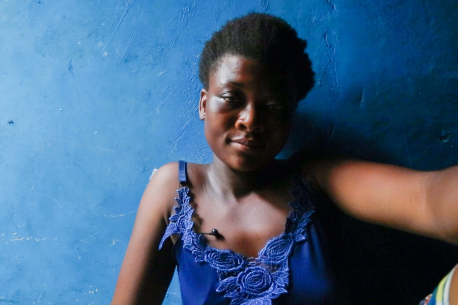 Salome Solomon sits in the room she shares with nine other girls in Accra's central market district.