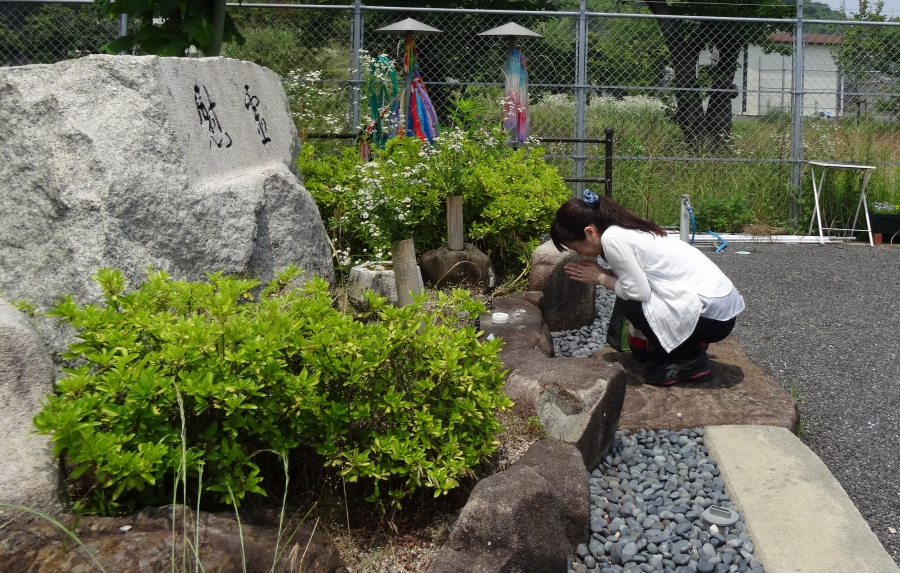 Aya Kano pays her respects at a shrine to the dead of Ninoshima.