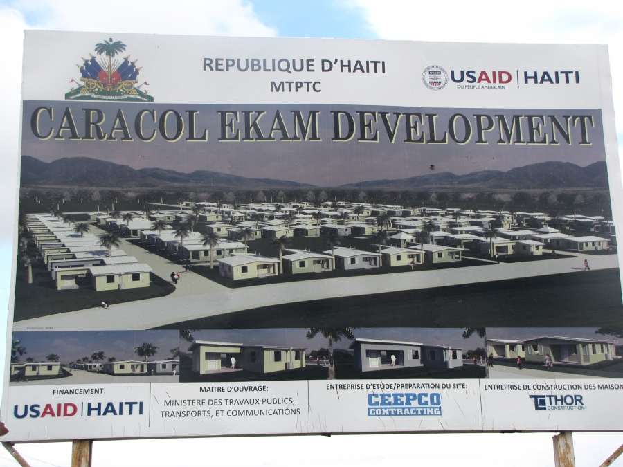 The sign outside Village la Difference, a USAID-funded housing project in Caracol, Haiti.