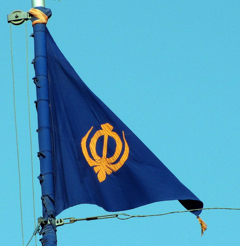 This Sikh flag, called the Nishan Sahib, is a another triangular flag from South Asia. It's made of cotton or silk cloth, with a tassel at its end. The word Nishan means symbol, and the flag is hoisted on a tall flagpole, outside most Gurdwaras, the place