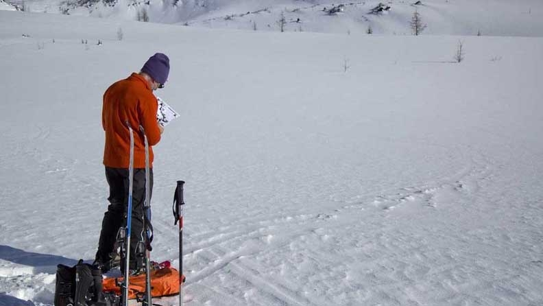 Simon Beck plots his course to begin his snow art project.