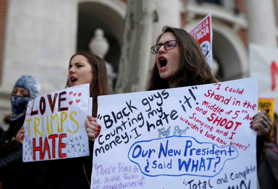 Women hold signs to show solidarity with the Women's March in Washington and many other marches in several countries, in Madrid, Spain