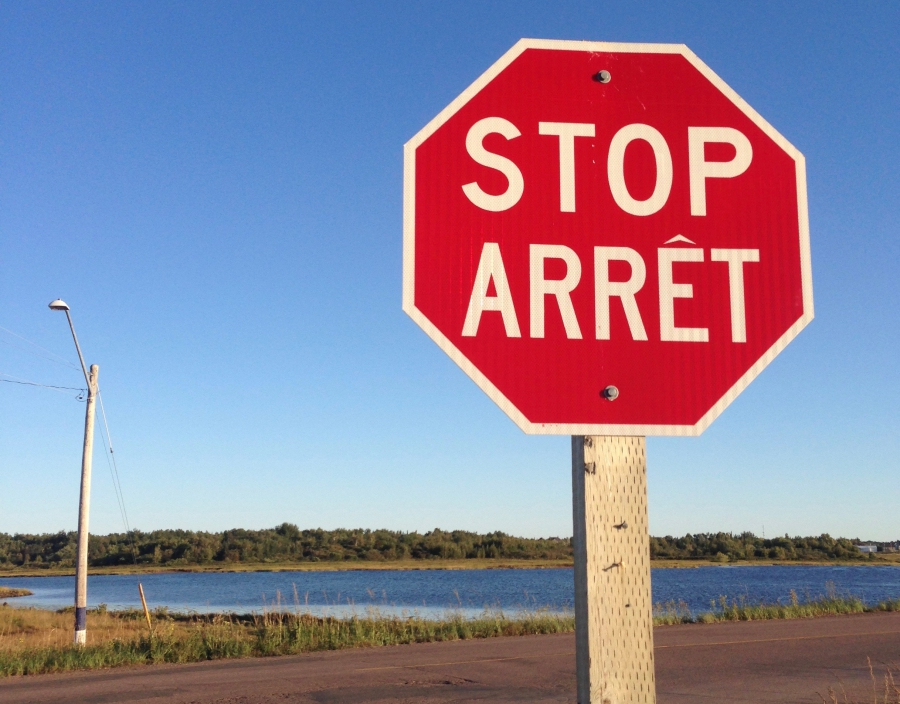 "In France, stop signs read ""Stop.""  In Quebec, they read ""Arrêt."" In New Brunswick, both words appear on stop signs."