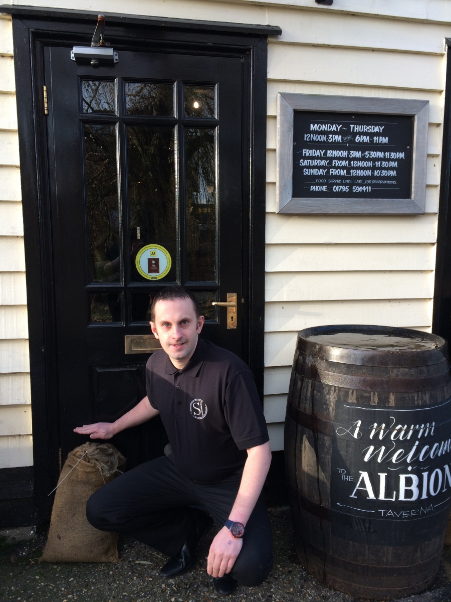 Gareth Finney shows the level of the floodwaters in his pub in Faversham England