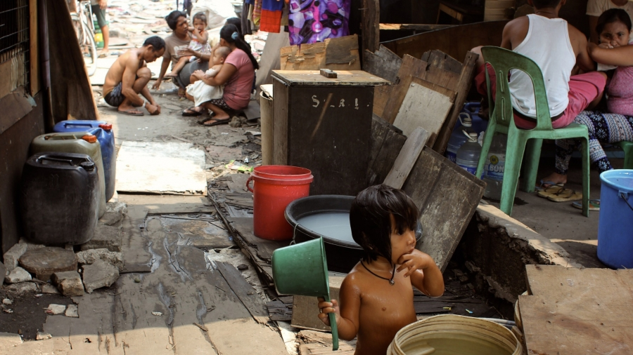 Ana Lisa Loste's daughter bathes in front of their house. It is not unusual for families in Tondo to have as many as eight or ten children.