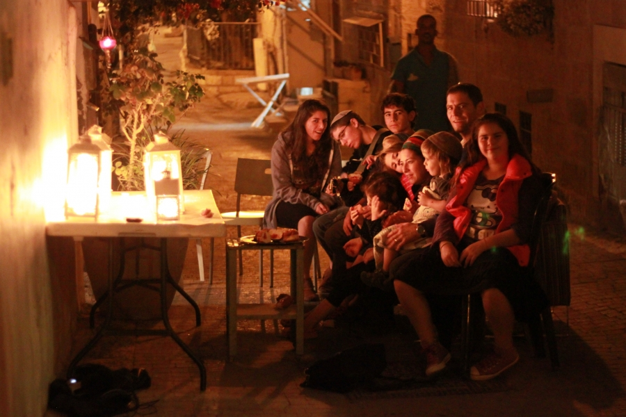 The Van Leeuwen family sits in front of the menorahs and sings.