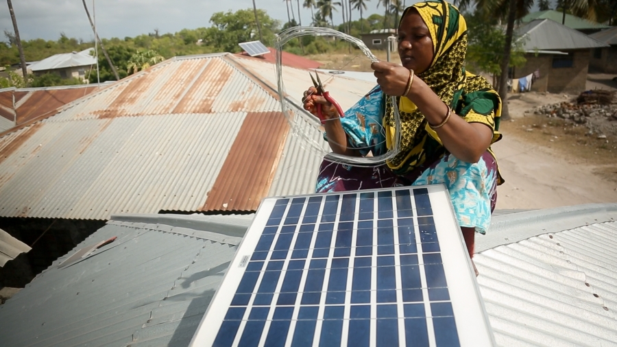 "Forty year old Mize Juma Othman installs a new photovoltaic panel on a home in Matemwe village, on the Tanzanian island of Zanzibar. Othman trained for six months in India to become one of the first 13 ""solar mamas"" in Zanzibar, able to install, troublesh"