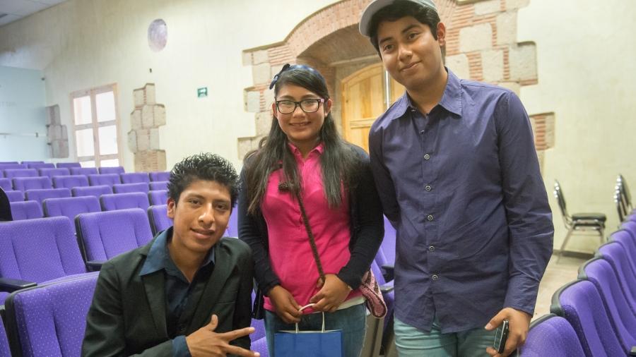 Three teens between a row of purple auditorium chairs