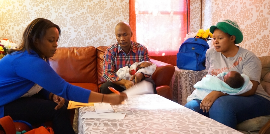 A woman sits on sofa across from man and woman, who each hold infants in their arms. Papers on the table.