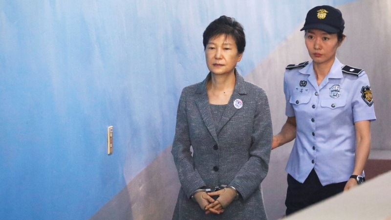 South Korean ousted leader Park Geun-hye arrives at a court in Seoul in handcuffs and escorted by a police officer.