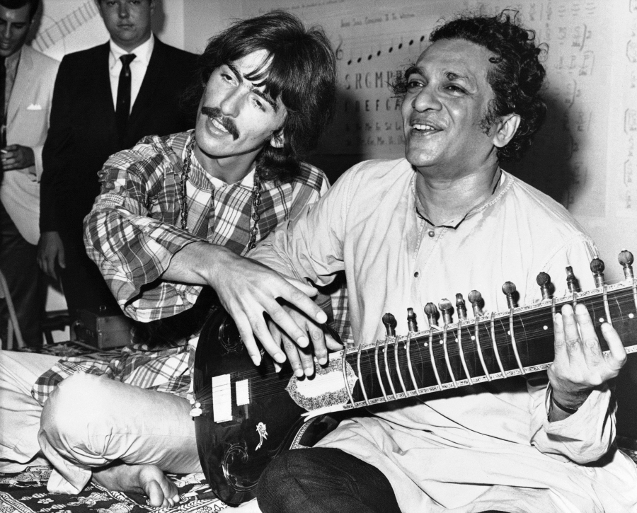 George Harrison of the Beatles sits cross-legged with his musical mentor, Ravi Shankar of India,