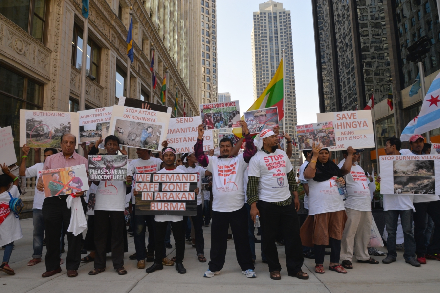 A wide shot of a people holding signs in front of a downtown Chicago skyscraper.