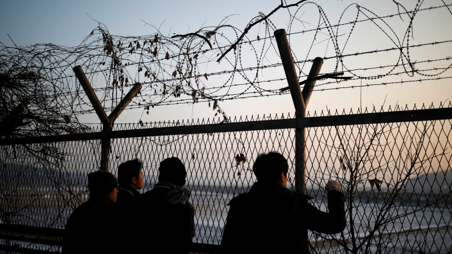 People look toward the north through a barbed-wire fence near the demilitarized zone separating the two Koreas, in Paju, South Korea.