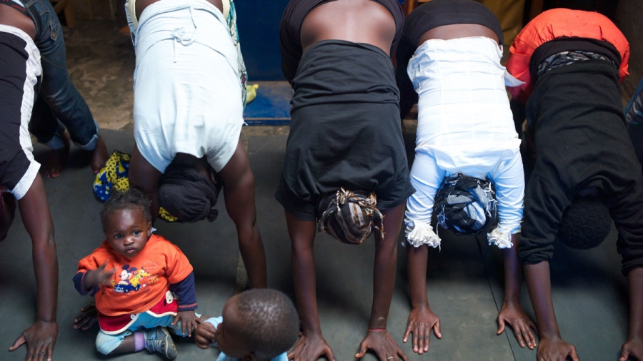 A yoga class for girls and young mothers in the slum of Kariobangi.  Mothers bring their kids to class.