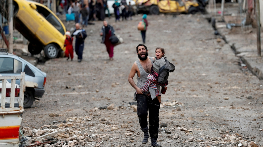 A man cries as he carries his daughter from an ISIS-held part of Mosul toward Iraqi special forces soldiers during a battle for the Iraqi city, on March 4.