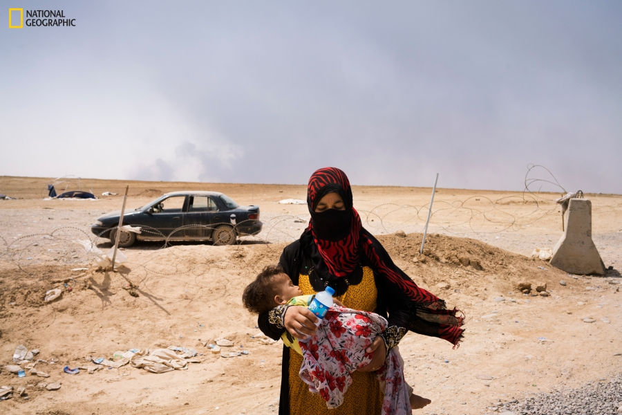 A woman and her child, having fled Qayyarah, arrive at a front line position.