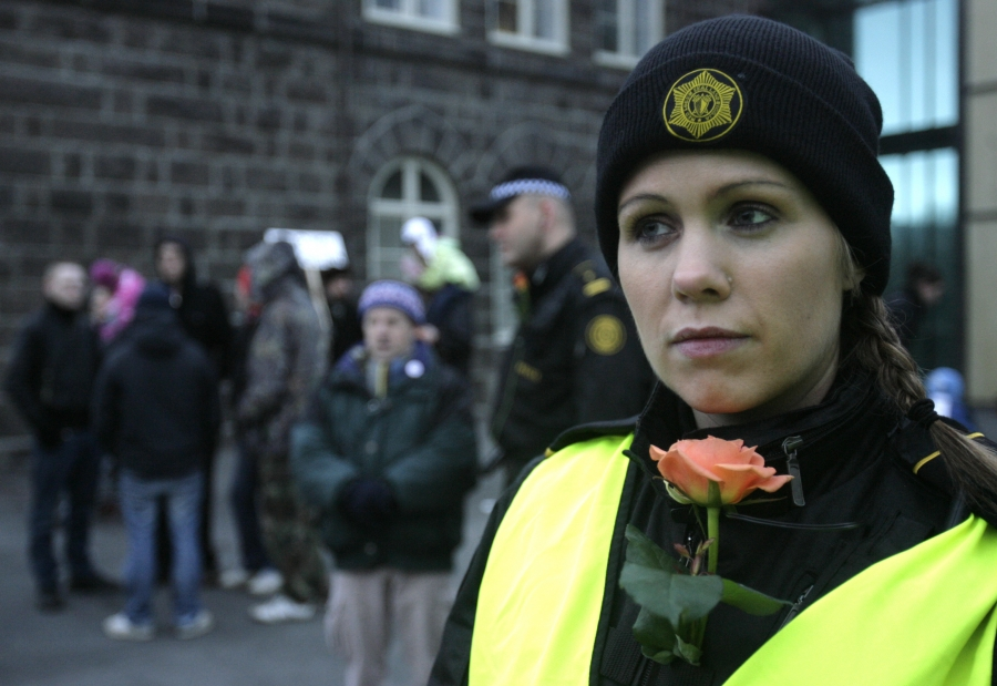 An Icelandic police officer stands guard at a peaceful protest near Iceland's Parliament house in Reykjavik