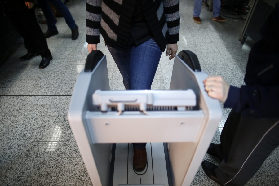 A woman goes through security checks at the Sarajevo International Airport in Sarajevo February 26, 2014.