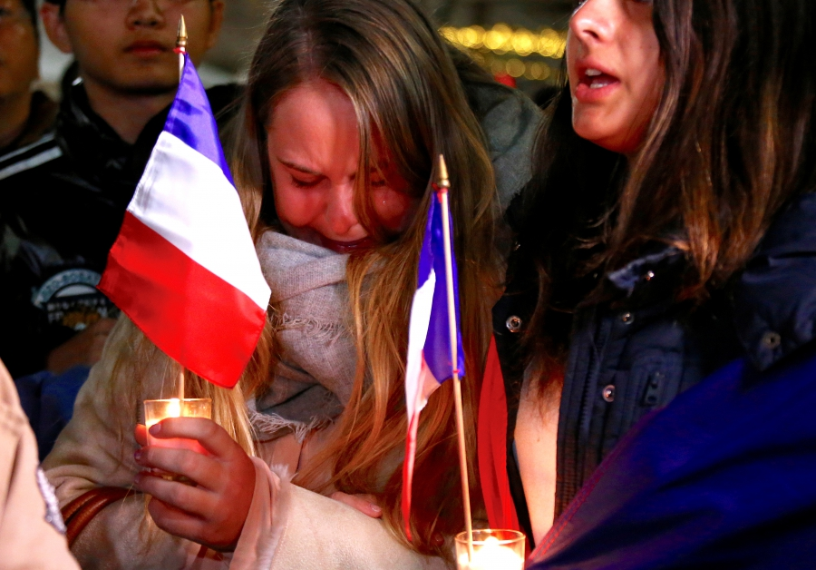 Members of the Australian French community cry as they sing the French national anthem during a vigil in central Sydney, Australia, July 15, 2016 to remember the victims of the Bastille Day truck attack in Nice. REUTERS/David Gray