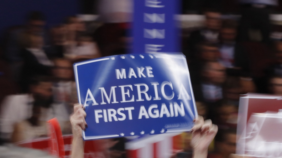 """A delegate waves a """"Make America First Again"""" sign at the Republican National Convention in Cleveland, Ohio, in July"""