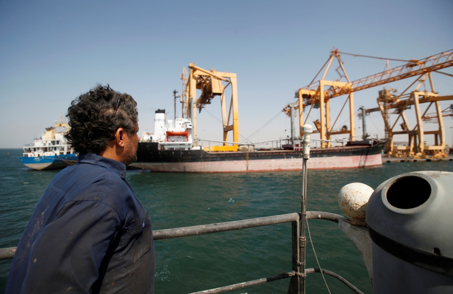 A Yemeni sailor looks at giant cranes, damaged by Saudi-led air strikes, at a container terminal at the Red Sea port of Hodeidah, Yemen