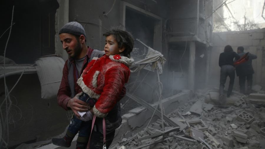 A man holds a child after an airstrike in eastern Ghouta, Syria, Feb. 7, 2018. In the Damascus suburb, besieged by government forces since 2013, about 78 civilians were killed by airstrikes and artillery fire on Tuesday, according to monitors. A further 2