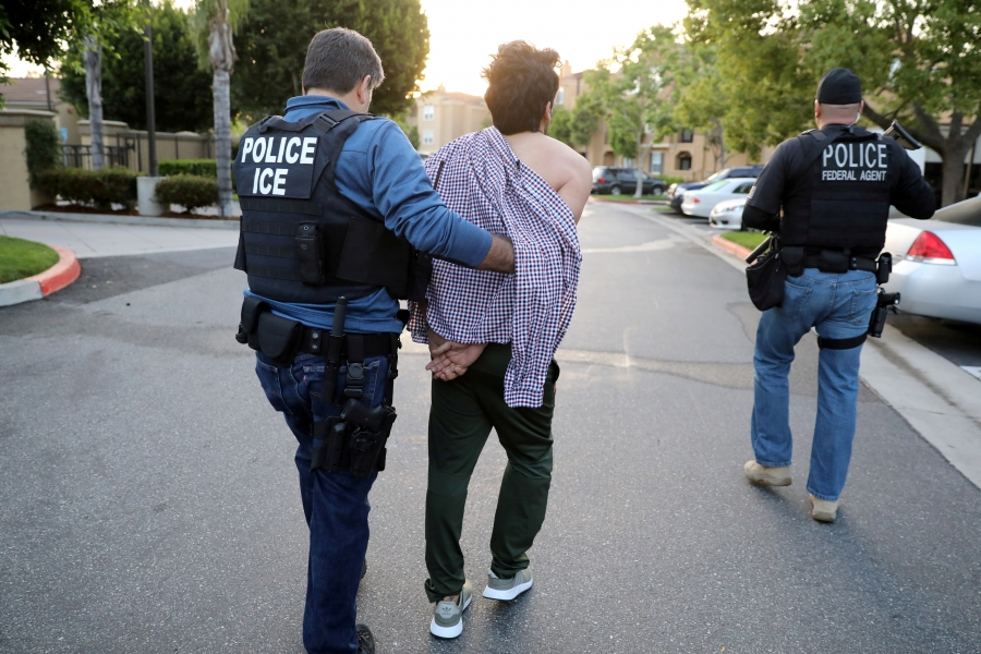 """A man with """"POLICE ICE"""" protective vest leads a man in handcuffs down street, with another officer with """"POLICE FEDERAL AGENT"""" on vest on the right"""