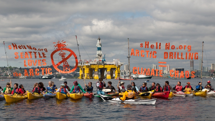 """Kayaktivists"" demonstrate in Seattle's Elliot Bay against the arrival last month of the Shell's massive Polar Pioneer oil rig, rising behind them above the city's waterfront. Shell is using Seattle as a staging area for its new offshore drilling operatio"