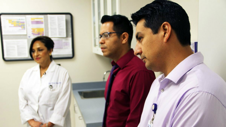 Two male and one female internationally trained doctors are listening to a presentation.
