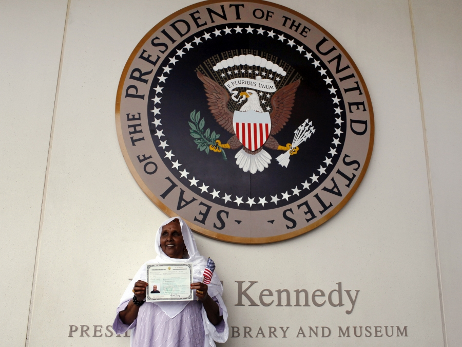 A woman holds up her certificate of U.S. citizenship