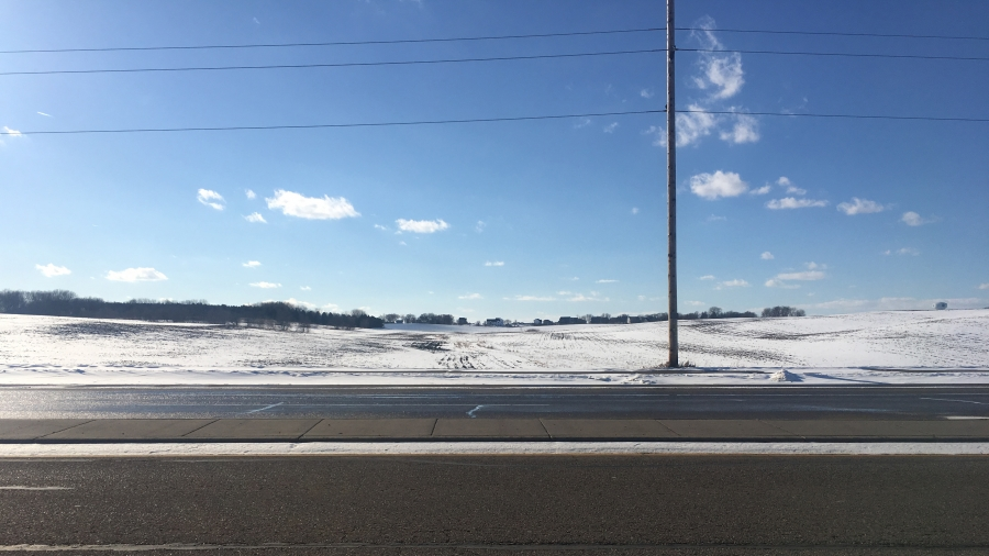 Sunshine on an empty road with snow-covered farmland in the background