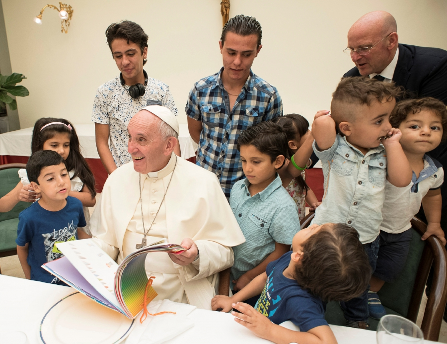 Pope Francis sits with some Syrian refugees