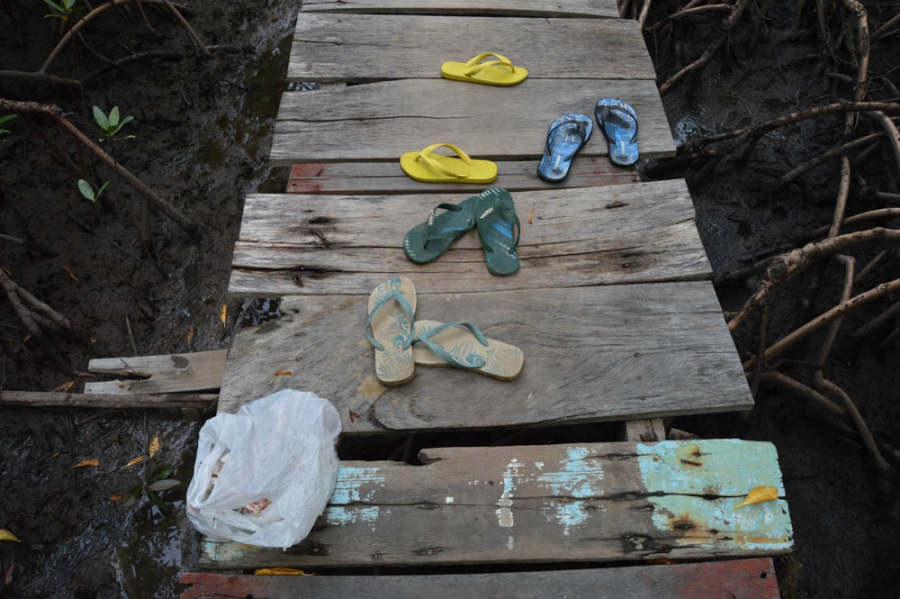 Children leave their flip-flops on the walkway through the mangrove swamp surrounding the fisherwomen's community.