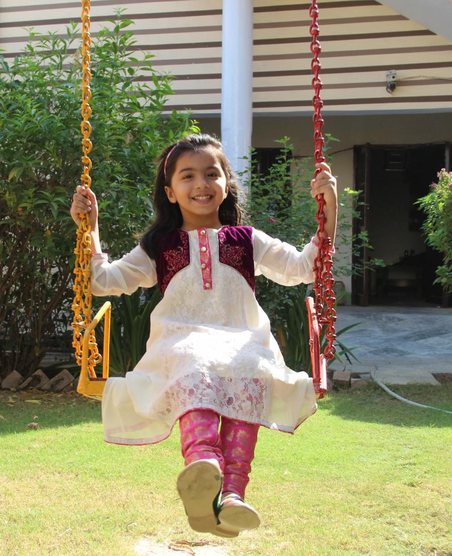 Umaima Awan swings outside her home