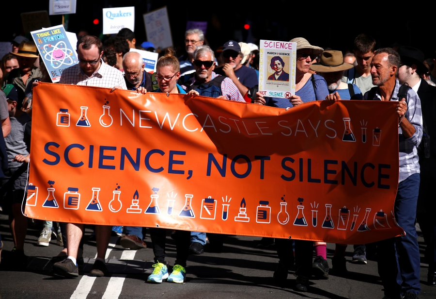 Protesters hold placards and banners as they participate in the March for Science rally on Earth Day, in central Sydney, Australia April 22, 2017.