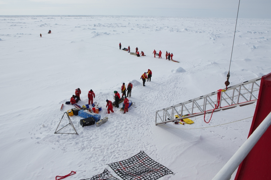 Crew and scientists traveling on the U.S. Coast Guard icebreaker Healy unload equipment in the lee of the parked ship before hiking off to set up their research projects in undisturbed snow.