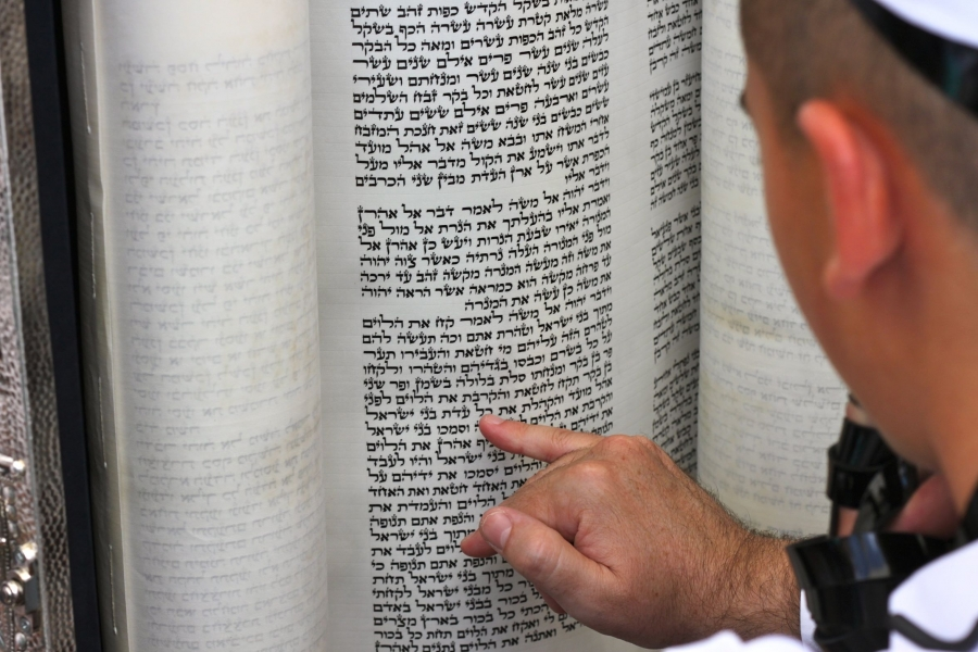 A boy reads the ancient Hebrew text from a Torah scroll at his Bar Mitzvah at the Western Wall holy site in Jerusalem.