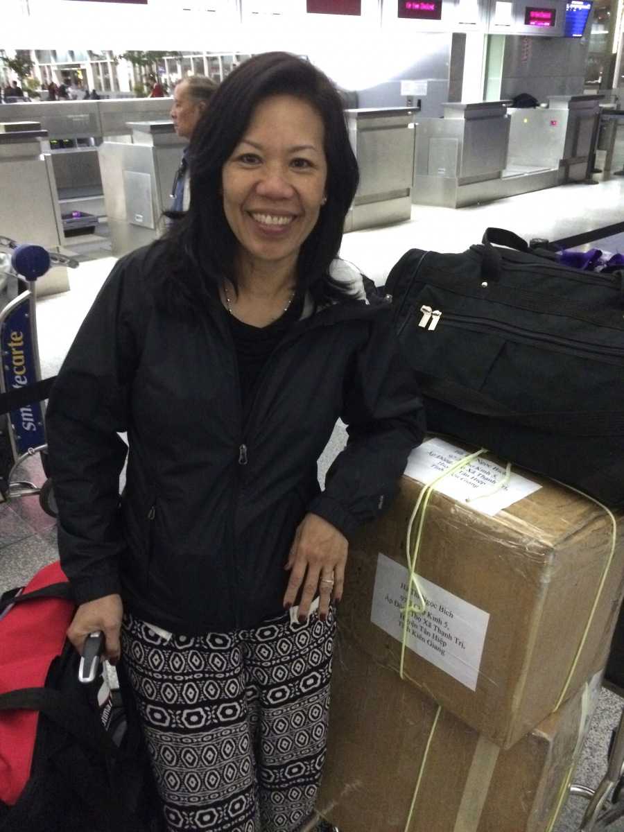 Ngoc Bich Ha stands in front of a conveyor belt with suitcases.