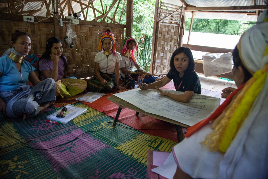 Women at Huai Sua Tao gather in a communal bamboo house for a meeting with province officials who came to gather information about their culture for educational purposes.