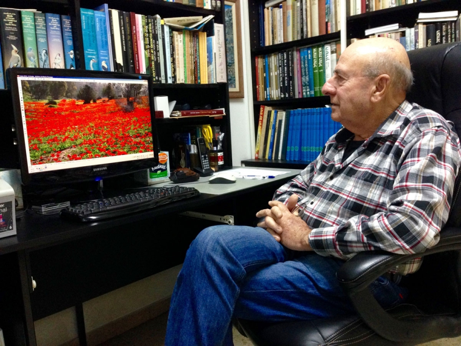 Uzi Paz, an Israeli wildflower expert, looks at a photo of Israeli wildflowers in his home in central Israel. Paz helped drive the campaign in the 1960s to outlaw wildflower picking.
