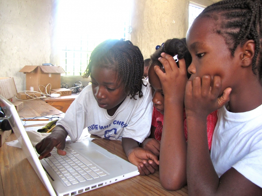 Frandy Calixte (right) with classmates at the Matenwa Community School learning numeration by playing a pirate video game translated into Creole by linguist Michel DeGraff and his team at MIT.