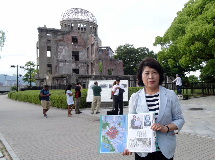 Hiroshima guide and 'memory keeper' Michiko Yamaoka holds a folder containing photos of her mother, who survived the blast, and her aunt, who died.